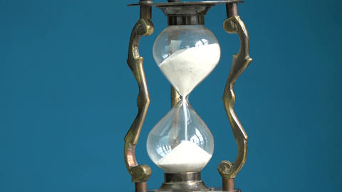 Rotating on blue background vintage brass hourglass and sand motion, 4K Footage