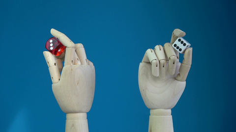 Rotating two wooden manikin hands with lucky dices Footage