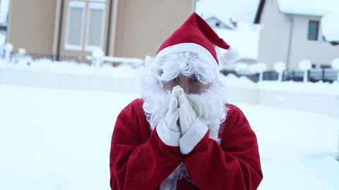 Santa Claus shivering and warm up with hands in front of snowy landscape Footage