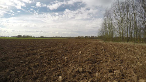 Freshly plowed field in early spring and clouds motion, time lapse 4K Footage