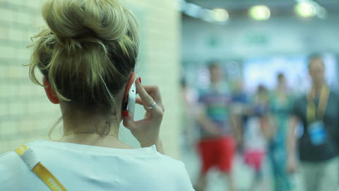 Backside View Blonde Woman in White T-shirt Talks on Phone Footage