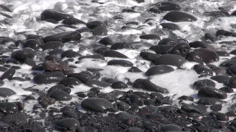 Wave foams on black pebbles Footage