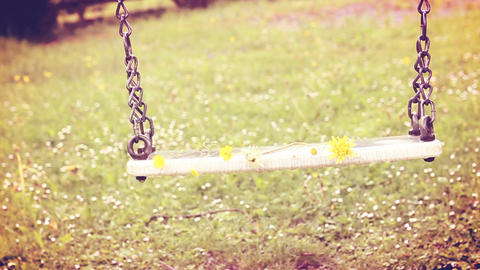 Empty swing moving with flowers in the spring season with warm creamy colors