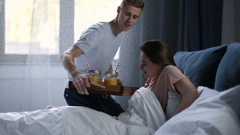 Smiling couple having breakfast in bed in morning