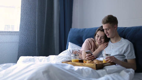 Joyful lovers having breakfast in bed at home