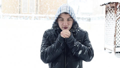 Young boy shivering and warm up with hands outside in snow falling Footage