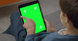 Boy using Tablet pc touchpad computer with Green Screen sitting on sofa