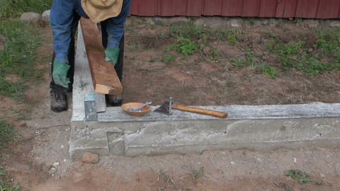 Builder placing wooden planks on cement foundation Live Action