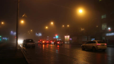 Fog in street of night city and cars on the road