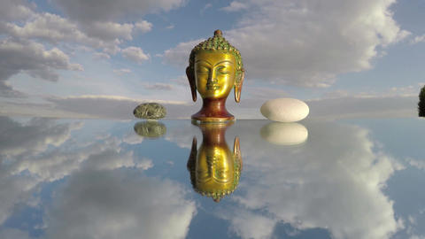 Buddha head sculpture and two stones on mirror, time lapse 4K Footage