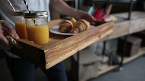 Delicious breakfast on wooden tray served by man Footage