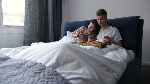 Cute couple surfing net with smartphones in bed, ライブ動画