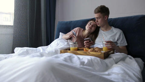 Cute couple surfing net with smartphones in bed Live Action