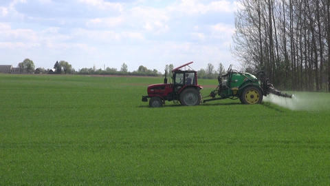 Tractor with reservoir spraying young wheat field Footage