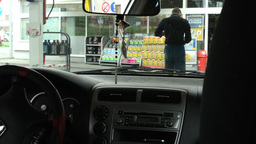 view from inside the vehicle - a man goes to pay for the gas station Footage