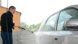 Man washing car with water (spray hose) Footage