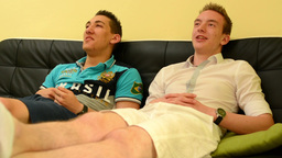 Two friends sitting on a couch and talking & watching TV (sports game) Footage