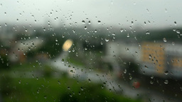 Timelapse: rain - water drops on the window(glass). City in background (blurred Footage