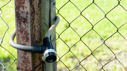 metal fence with a lock - in the background of grass Footage