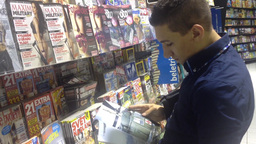 man looks at a magazine in a newspaper shop Footage