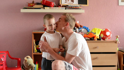 Young man plays with child (small boy) in the room - they kiss Footage