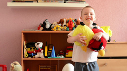 child plays with toys in room and smiles and jump - stuffed toy (angry birds) Footage