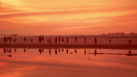 Burmese village youth and young monks playing football at sunset. Myanmar Footage