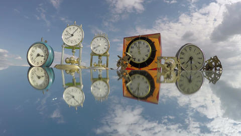 Many clocks on the mirror beneath the cloudy sky, time lapse 4K Footage