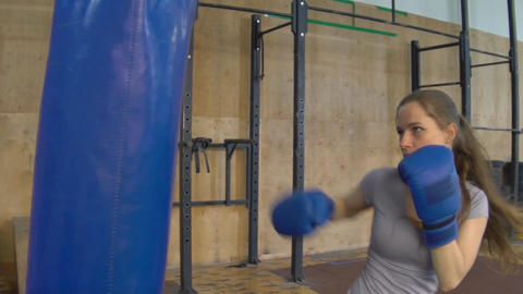 Slow Motion Sports Woman Is Engaged In Boxing, Trains With A Boxing Bag Footage