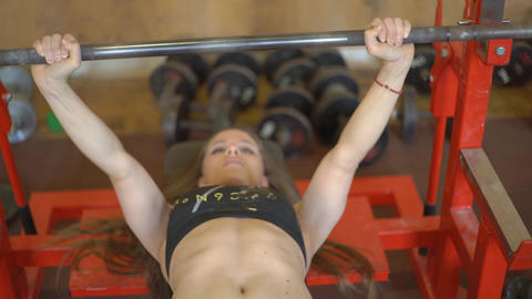 Attractive Female Athlete Doing Barbell Bench Press In The Gym Footage