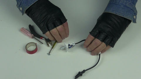 Man wearing black gloves fixing electrical plug Footage
