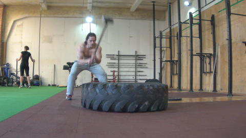 Slow Motion Young Man Working Out, Hitting Tire With Sledgehammer Footage