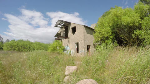 Old desolate building in the green meadow on breezy sunny day, time lapse 4 k Live Action