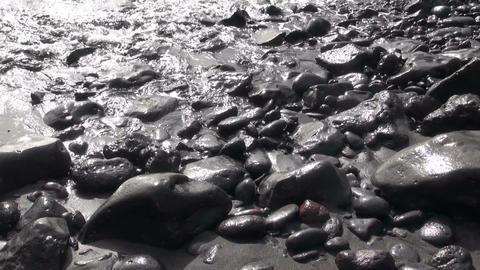 Waves crashing on large pebbles and stones Footage