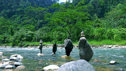 pyramids made of rocks balancing on top of each other standing in shallow river Footage