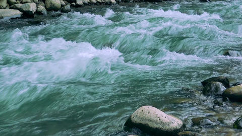 Shot of fast fresh torrent of tropical river foaming while flowing over stones Archivo