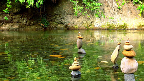 Stones stacked into pyramid on bank of tropical pond. Harmony and tranquility Footage