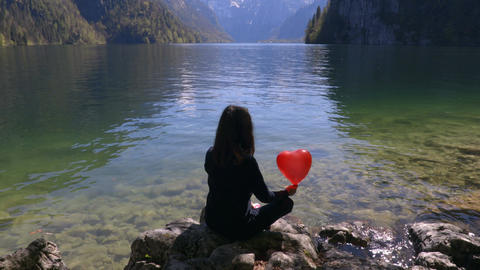 Young girl with red balloon in shape of heart in nature next to the lake Footage