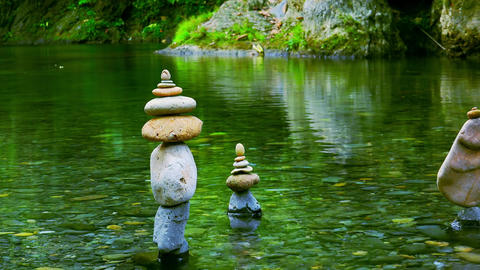 Stones stacked into pyramid on bank of tropical pond. Harmony and tranquility Live Action
