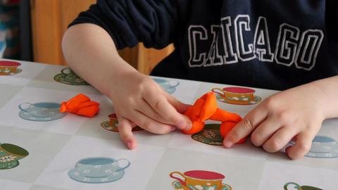 Child Modeling Orange Clay Image