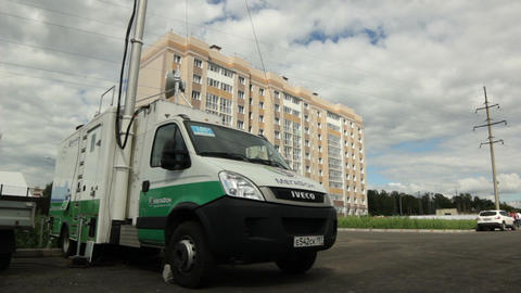 Brand Minibus with Antenna Stands against Large Building Footage