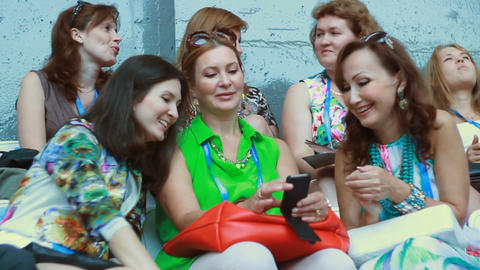 Joyful Women in Stylish Dresses Sit and Look at Mobile Phone Footage