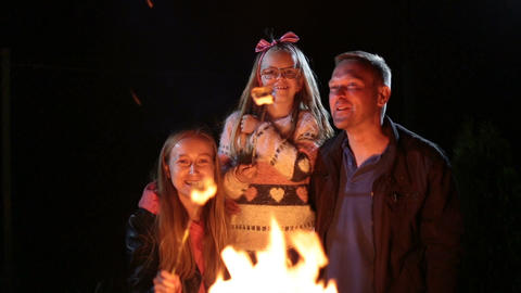 Happy family roasting marshmallow over campfire Footage