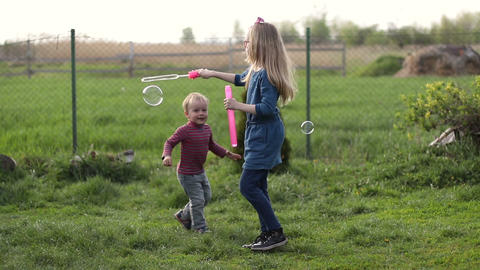 Happy cute children playing with bubbles in yard Footage