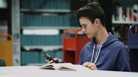 Teenage boy studying book in library Footage