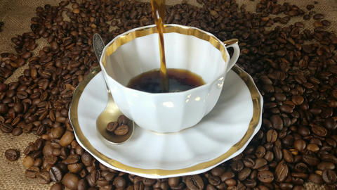 Pouring fresh brewed coffee into the coffee cup in slow motion Footage