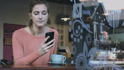 Young adult woman looking at smart phone in café ライブ動画