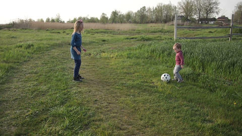 Cute siblings playing football together outdoor Footage