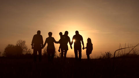 Three generation family walk in meadow at sunset Footage