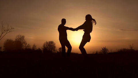 Couple in love whirling on the meadow at sunset Footage